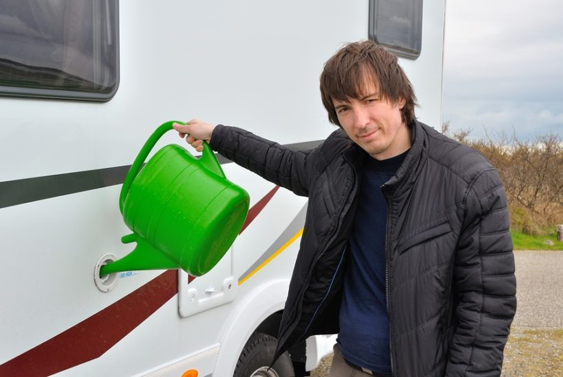 man with water tank and rv